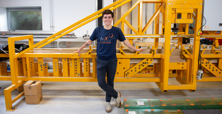 A beX scholar, Victor Henquel, poses next to a wood bending machine