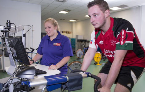Staff and an athlete working with exercise bike in sports science lab