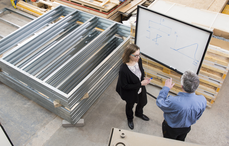 Engineers working in front of a whiteboard in a warehouse