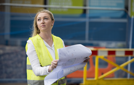 Woman in hi viz holding engineering drawings