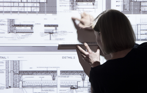 Architect pointing to part of projected building plans
