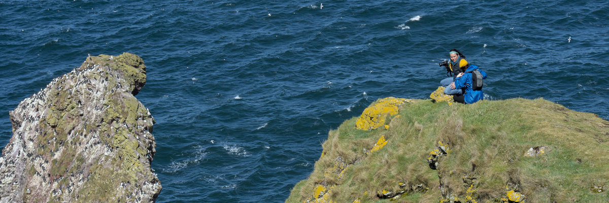 Two students photographing wildlife on the cliffs at St Abbs