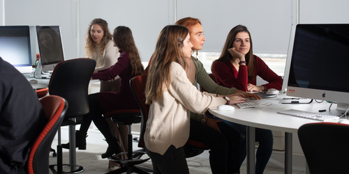 A class of female students working on Apple computer
