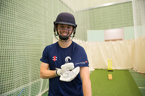 A batsman shows the Edinburgh Napier logo