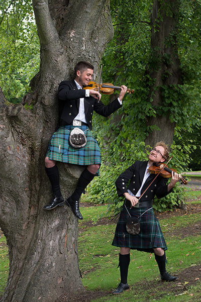 Two Scottish guys wearing kilts and playing the violin outside
