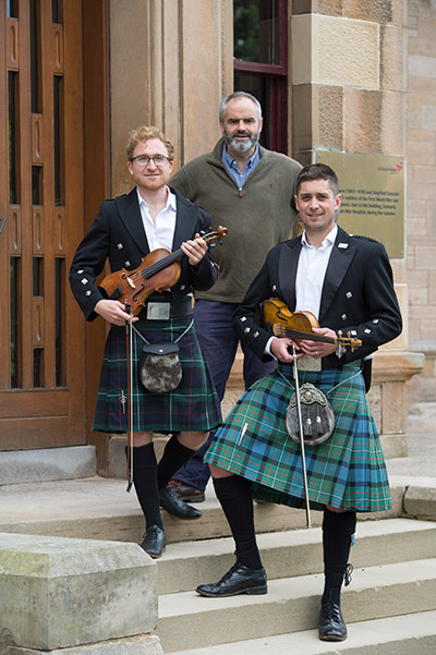 Scottish guys in kilts and holding violins in front of a building