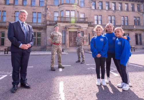 Suited politician, two uniformed soldiers and three uniformed school children in front of old military hospital at Craiglockhart