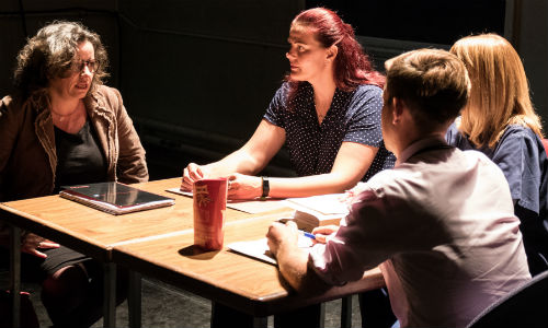 The play Cracks being performed, four actors in discussion around a table