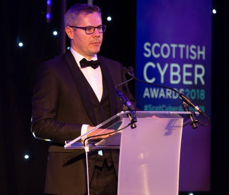Derek MacKay at the lectern, speaking at the Scottish Cyber Awards 2018