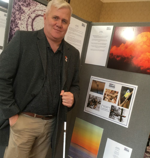 Dave Phillips beside a display board with his poems and other art