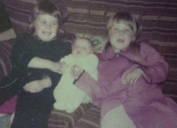 Kerri and Colene as children; Kerri in a blue dressing gown, Colene as a baby and their other sister Kelli is in pink.