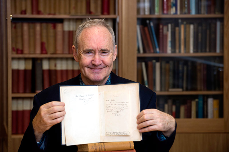 Nigel Planer with a previously unseen letter written by Robert Louis Stevenson in a room dedicated to the University's Mehew Collection