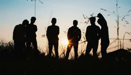 Six young people in silhouette in an outdoor setting