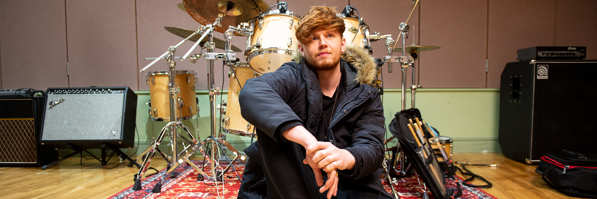 Image of Jordan Harvey in front of drum kit at Edinburgh Napier University music studio